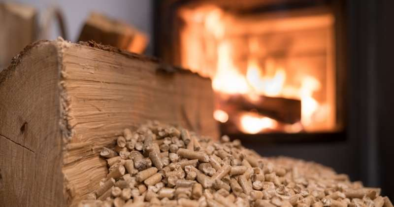 Wood stove pellets and log in front of fire